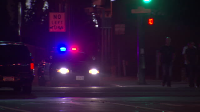 vidéos et rushes de police car w/ illuminated emergency & headlights stationed at intersection as lone suv passes by and pedestrians cross street - phare de véhicule
