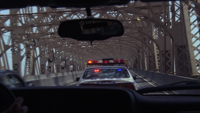 A police car with its lights flashing speeds across the Queensboro Bridge during a pursuit.