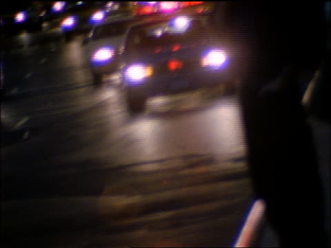 police car with lights flashing driving on street towards camera at night / new york city - 犯罪点の映像素材/bロール