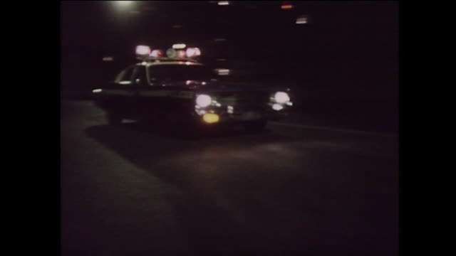stockvideo's en b-roll-footage met police car with sirens drives past at night: new york, 1975 - criminaliteit