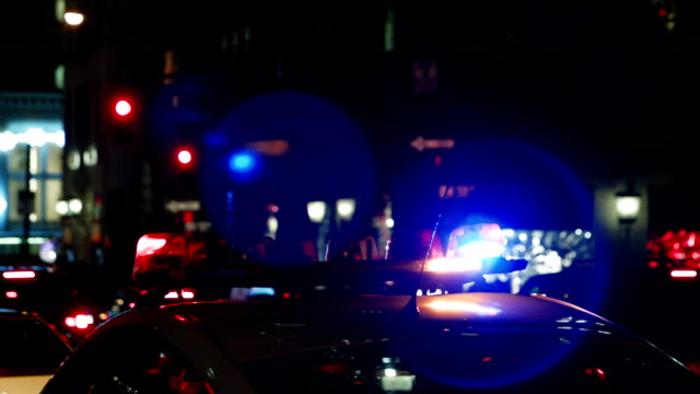 Police car with turned on siren at night street