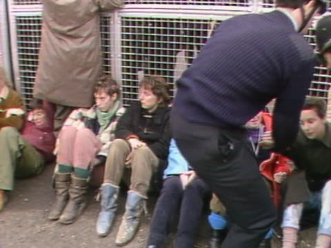 police carry anti nuclear protestors away from the gates of greenham common airbase - nuklearbombe stock-videos und b-roll-filmmaterial