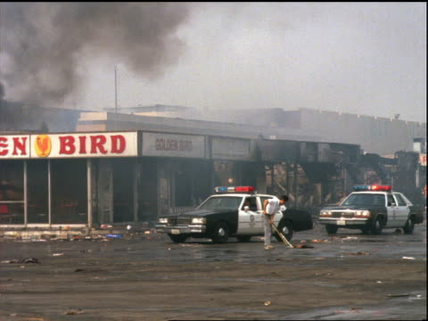 vídeos de stock e filmes b-roll de of police cars drive thru parking lot of burnt mall / los angeles riots - 1992