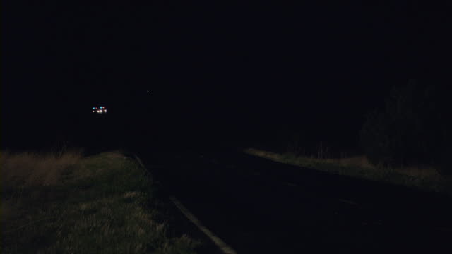 Police cars moving on a road at night.