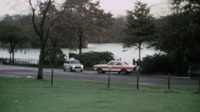 ws police cars parked by a lake park after finding a body / united kingdom - police car stock videos and b-roll footage