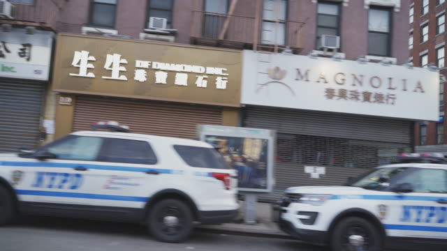 police cars parked on the street in front of closed stores in chinatown manhattan during the city partial lockdown during the coronavirus outbreak. - chinatown stock videos & royalty-free footage