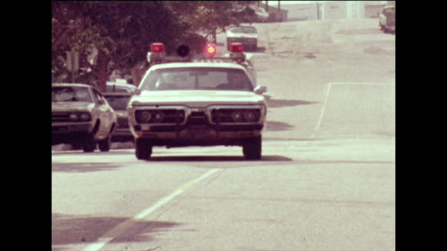 police cars pull up outside a residence in the us; 1973 - audio available stock-videos und b-roll-filmmaterial