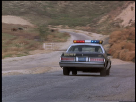Police cars speed along curvy, rural roads.