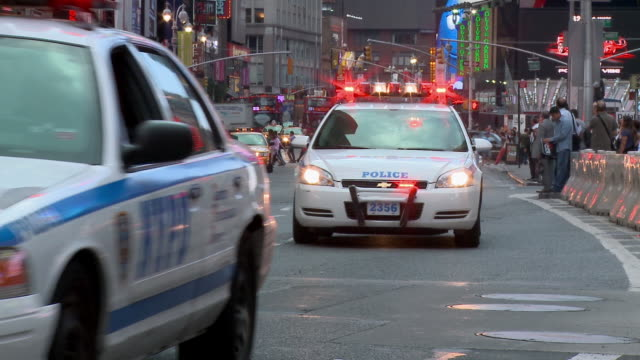 ms, police cars with flashing emergency lights driving on broadway street, new york city, new york, usa - police car stock videos & royalty-free footage
