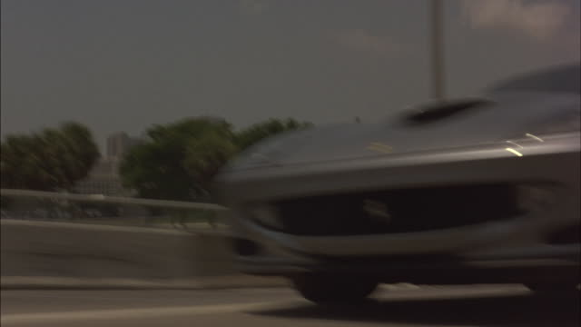 Police chase a silver sports car on a highway.