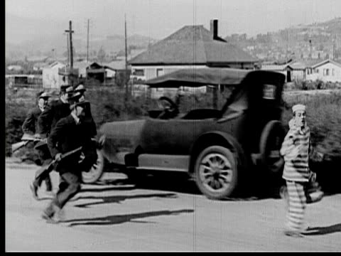 1925 B/W WS TS PAN Police chasing prisoner down street / Los Angeles County, California, USA