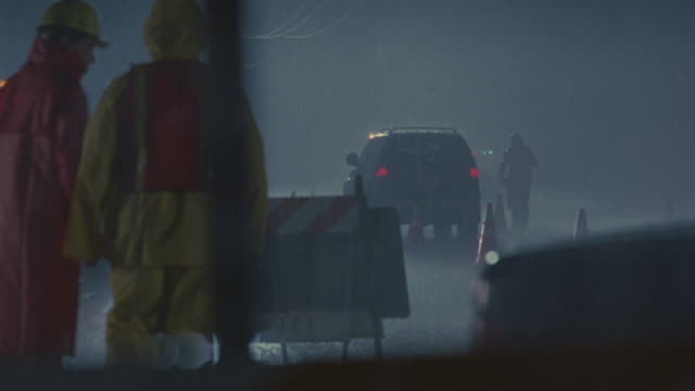 A police checkpoint regulates traffic during a rain storm.