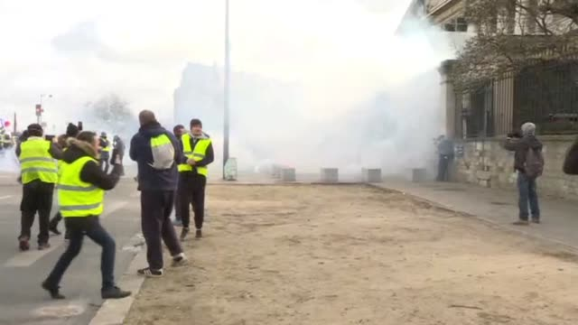 Police clash with yellow vest protesters outside the National Assembly in Paris during the 13th weekend of demonstrations
