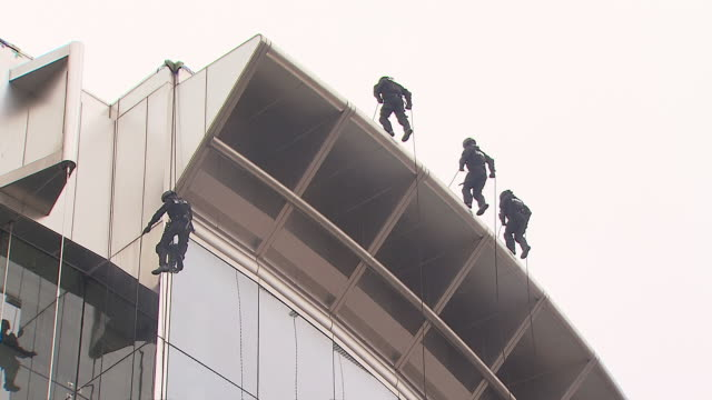 vídeos de stock e filmes b-roll de ms ts police commando repelling down high-lines from building / incheon, south korea - menos de 10 segundos