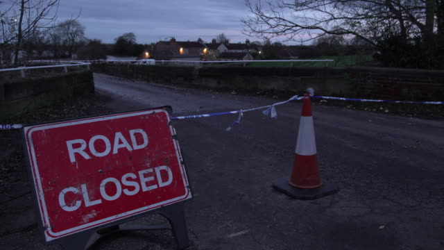 police cordon tape and a road closed sign mark no access on a bridge leading to the south yorkshire village most affected by flooding. a power... - road closed englisches verkehrsschild stock-videos und b-roll-filmmaterial