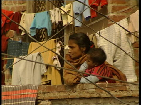 Police corruption allegations in case of murdered slum children Debris and litter in street in slum area Woman stands with baby on balcony of slum...