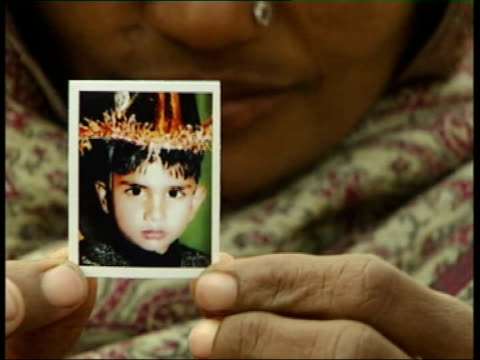 police corruption allegations in case of murdered slum children ashok kumar sits in alleyway mother holds up small photograph of her missing son max... - ineptitude stock videos & royalty-free footage