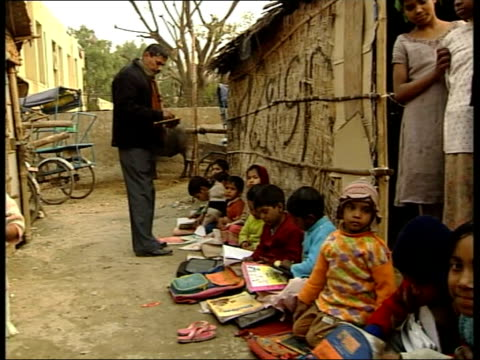 Police corruption allegations in case of murdered slum children Children playing in back alley Children seated on ground in alley with books on their...