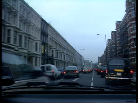 London Police along road thru heavy traffic flashing headlights and with siren sounding Cars and buildings passing TRACK