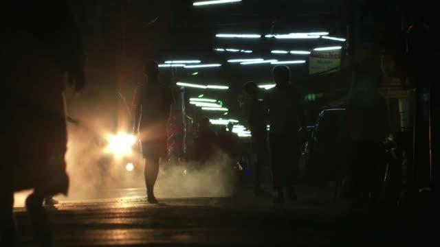 vídeos y material grabado en eventos de stock de police crackdown on student activists chime being struck at temple woman praying people crossing footbridge with temple seen behind woman smoking... - t mobile