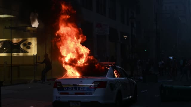 police cruiser of the philadelphia police department is on fire while looters enter the apple store on walnut street during black lives matter... - looting stock videos & royalty-free footage