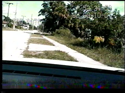 / police dashcam footage of a car driving through intersection hitting motorcyclist and knocking him into the air / suspect crashes into a yard and...