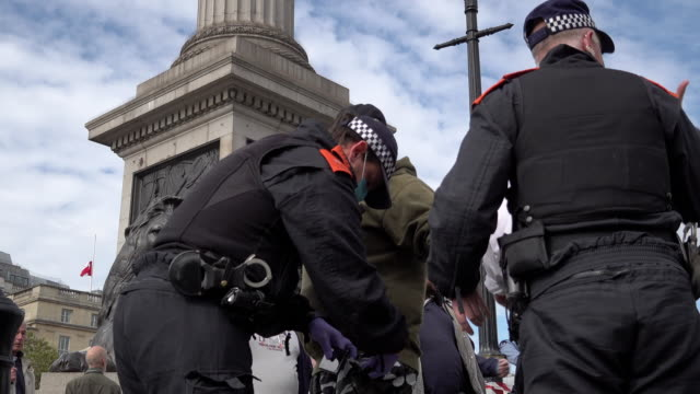 police detain a man, confiscate a riot shield and search him on suspicion of having a weapon as thousands of people gather on trafalgar square for a... - weaponry stock videos & royalty-free footage