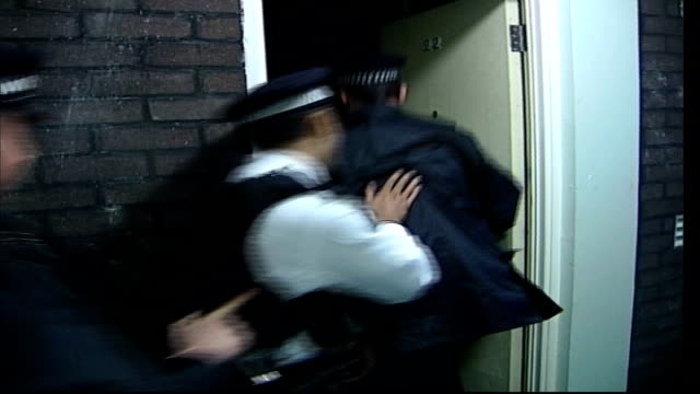 ext police officers break down front door and enter flat during drugs raid police officer handcuff male suspect lying on floor of flat - face down stock videos & royalty-free footage