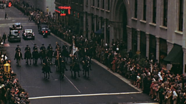 vidéos et rushes de police escort on horseback and motorcycle through city street crowded with spectators / new york city new york united states - 1945
