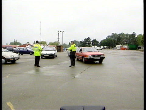 Police find a body ITN ENGLAND Northamptonshire Great Billing Billing Aquadrome Policeman allowing car thru checkpoint CMS Policeman checking boot of...