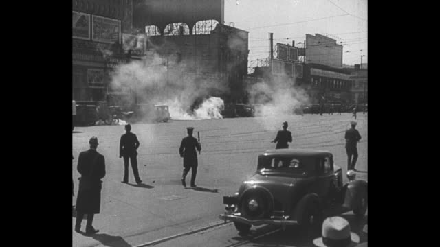 WS police fire tear gas canisters in San Francisco street during longshoremen's strike / side view officer in plainclothes shoots tear gas canister /...