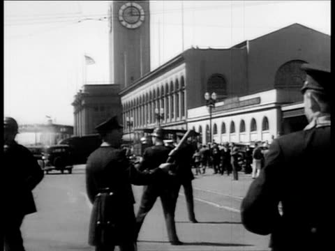 vídeos y material grabado en eventos de stock de police firing guns at rioting crowd in front of ferry building / police firing guns during violent longshoreman and dock workers strike / people... - 1934
