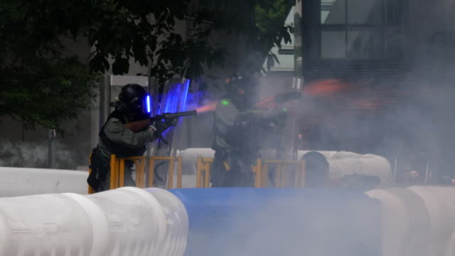 police firing tear gas at protesters from the roof of the hong kong government headquarters - demonstrant stock-videos und b-roll-filmmaterial