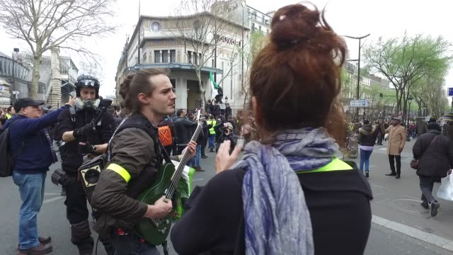 vídeos de stock, filmes e b-roll de police force with yellow vests and a guitarist in the barbes district in paris - vest