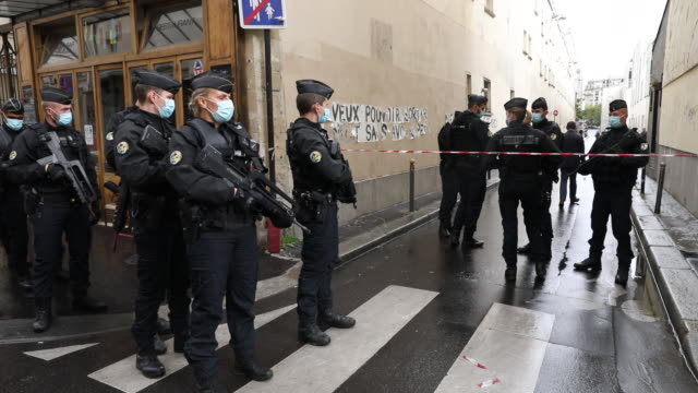 police forces patrol near the scene of an attack in which several people were injured near the former offices of the french satirical magazine... - satira video stock e b–roll