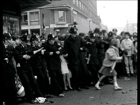 vídeos de stock e filmes b-roll de police form human barrier and hold back crowds of beatles fans as they try to push through birmingham 1963 - 1963