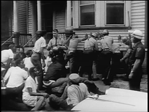 b/w 1967 police frisking black men leaning against house after newark race riots nj / newsreel - 1967 stock videos & royalty-free footage