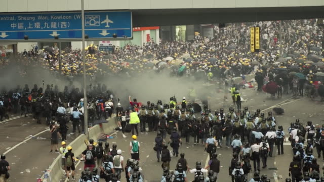 police get protest riot over extradition bill under control by launching tear gas and pushing back protesters - hong kong stock videos & royalty-free footage