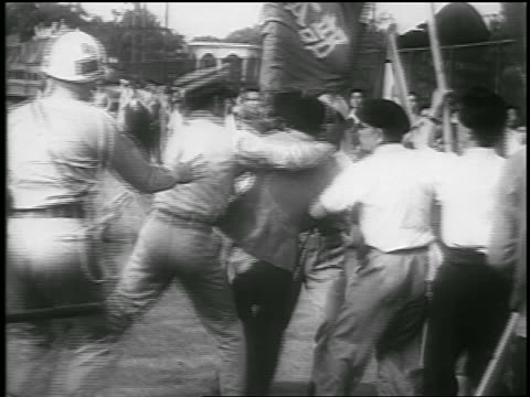 B/W 1950 police grabbing trying to pull man away from Communist demonstration / Japan / newsreel