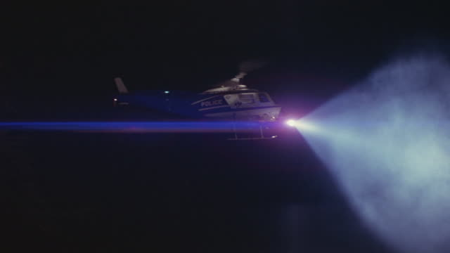 vídeos de stock e filmes b-roll de a police helicopter conducts a search with a spotlight. - helicóptero