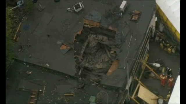 helicopter removed from building air view of hole in roof where helicopter crashed - ヘリコプター事故点の映像素材/bロール