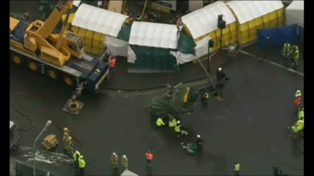 helicopter removed from building air view of helicopter wreckage hanging on crane above road pull out crash scene - ヘリコプター事故点の映像素材/bロール