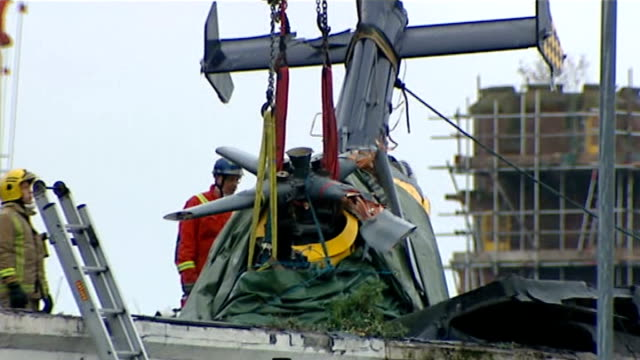 helicopter removed from building scotland glasgow ext rescue team on roof with part of helicopter suspended in chains / tail boom in chains slowly... - ヘリコプター事故点の映像素材/bロール