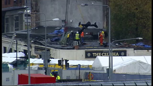 helicopter removed from building scotland glasgow ext high angle shot helicopter winched off pub rooftop - ヘリコプター事故点の映像素材/bロール
