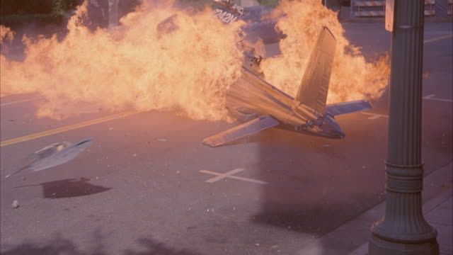 A police helicopter crashes and explodes on a city street as a taxi cab skids to avoid the wreck.