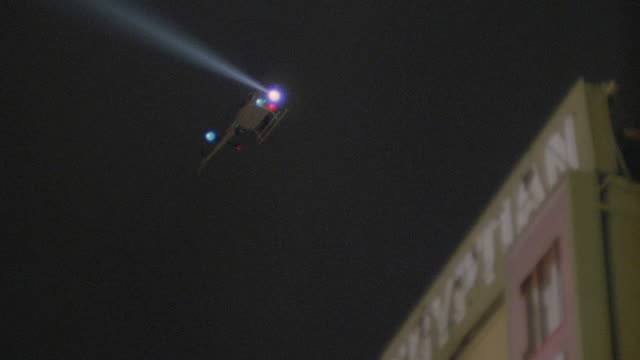 a police helicopter flies above the egyptian theater and sweeps its searchlight overhead. - suchscheinwerfer stock-videos und b-roll-filmmaterial