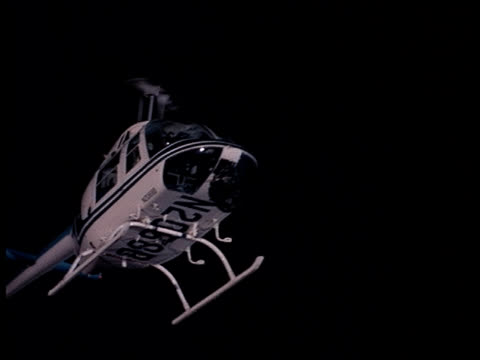 a police helicopter hovers in the night sky. - suchscheinwerfer stock-videos und b-roll-filmmaterial