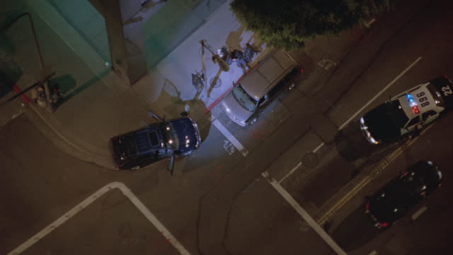A police helicopter hovers over a crime scene as a suspect drives away in a car.