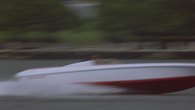 a police helicopter pursues a speedboat across biscayne bay. - motoscafo da competizione video stock e b–roll