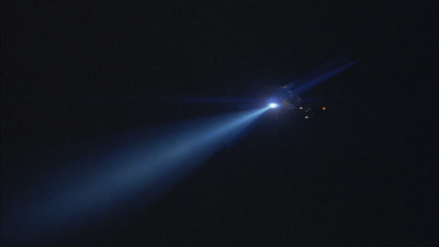 vídeos de stock e filmes b-roll de a police helicopter shines a search light on the ground. - helicóptero